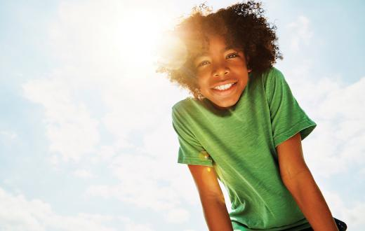 boy leaning over smiling at the camera backlit by a sunny blue sky