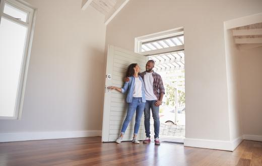 happy smiling couple opening the door to their new home