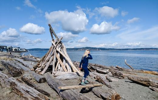 Girl on Bainbridge Island beach climbing on driftwood Explore Bainbridge spring break activity kit
