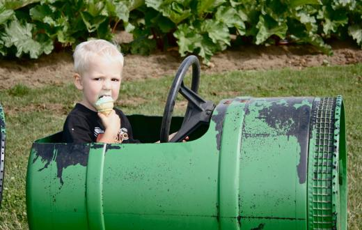 Young boy enjoying an ice cream cone at a playground in Lynden, Washington
