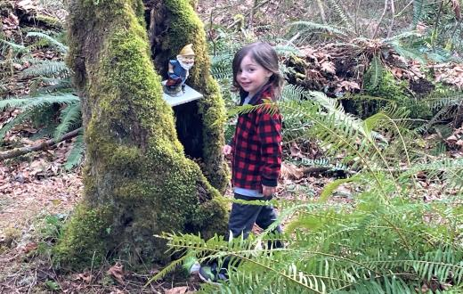Kid in plaid jacket standing by gnome in tree along Maple Valley gnome trail fun for Seattle-area families