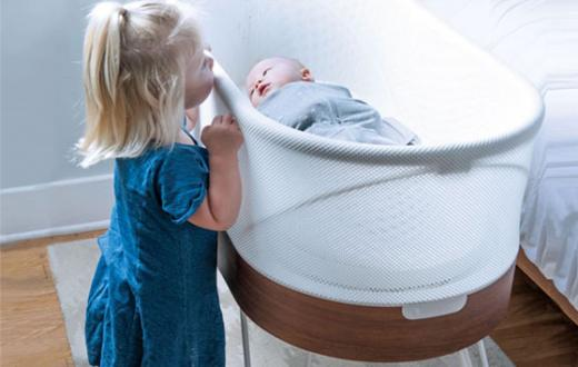 Little girl peeking over looking at sleeping baby in a SNOO bassinet