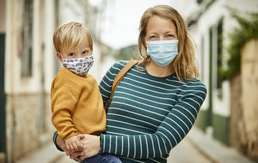 mother holding her son outdoors, both of them smiling under masks