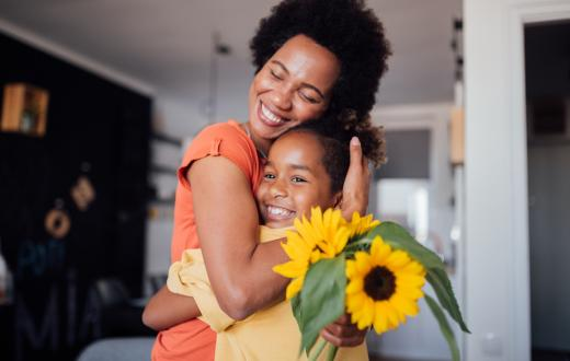 mother and daughter hugging with a vase of sunflowers on the kitchen table