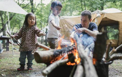 Dad-and-kids-setting-up-camp-fire