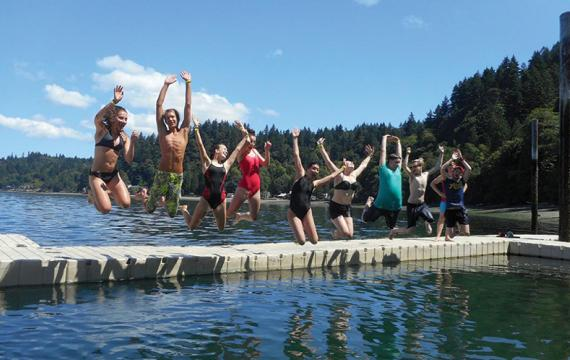 Summer campers jumping into water