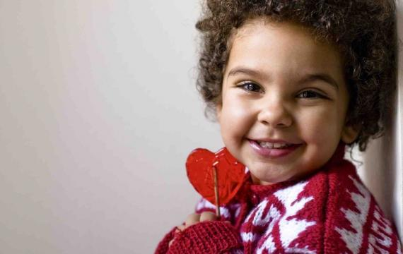 Valentine's Day kid holding heart-shaped lollipop