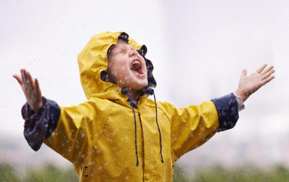 Boy out in the rain with raincoat on