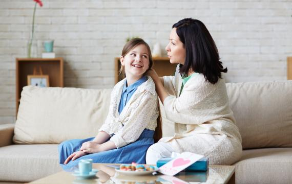 mom and daughter talking on couch