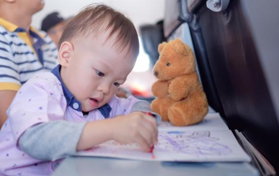 Toddler coloring on plane