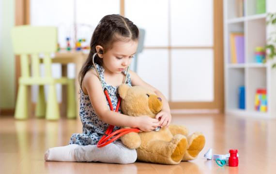 girl holding stethoscope to teddy bear