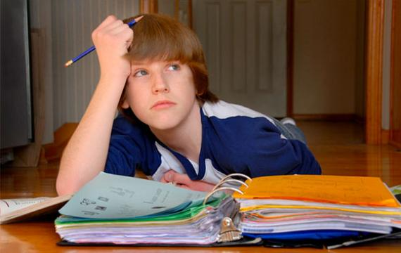Upset teen boy doing homework