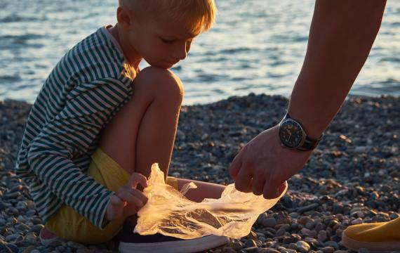 A young boy helps his father collect garbage on the beach at sunset