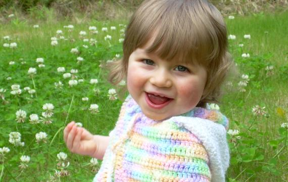 Little girl playing in a clover field