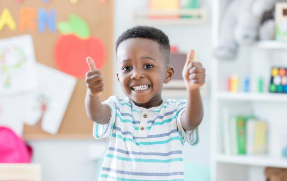 Boy holding two thumbs up at preschool