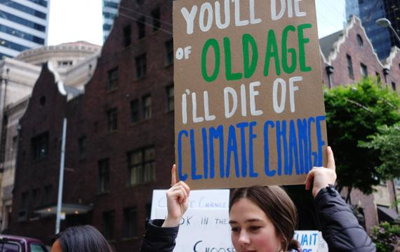 Young woman holding a sign at a climate action strike