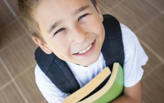 boy holding books and smiling