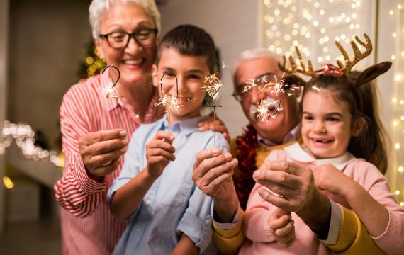 grandparents with grandchildren holding new year sparklers