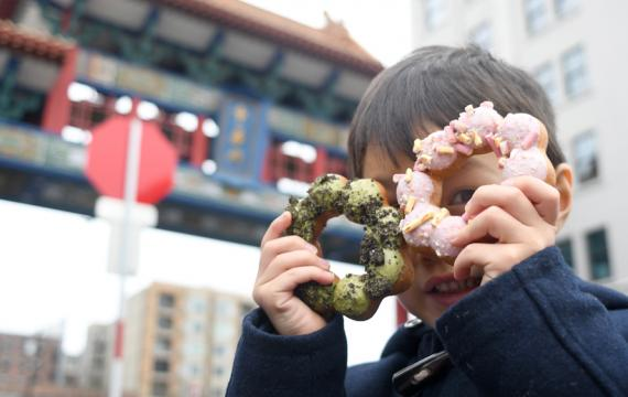 kid holding dochi mochi doughnuts up to his face best eats with kids in seattle's chinatown international district