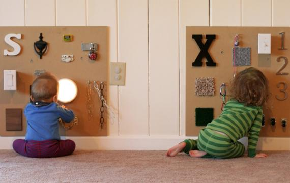 sensory boards mounted on a wall with toddlers playing