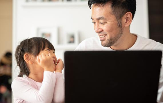 father and daughter sitting at a table in front of a laptop having fun