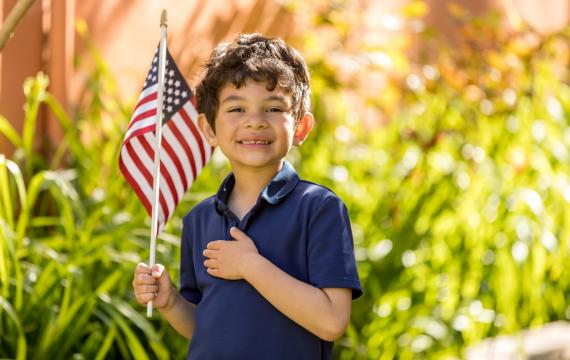 little boy holding an american flag