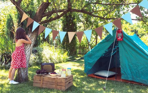 girl standing by tree with tent in backyard for backyard campout