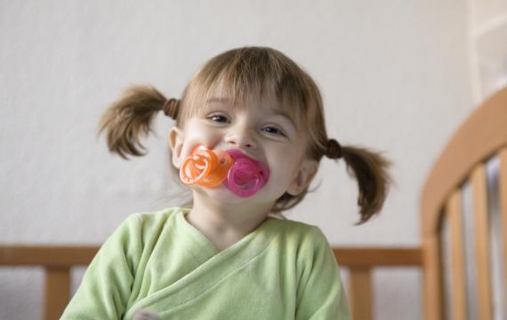 silly girl with two pacifiers in her mouth smiling