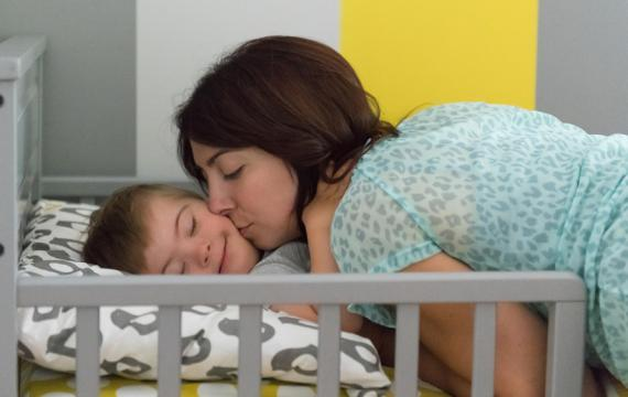 mother kissing her child with down syndrome at naptime
