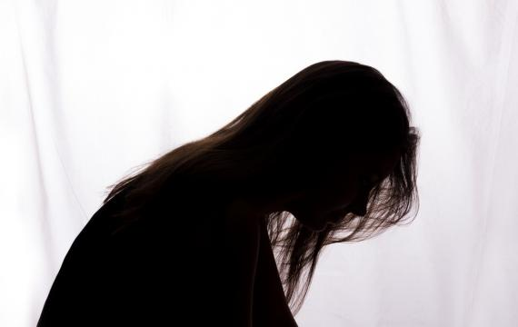 silhouette of a woman bent forward with hair falling across her face