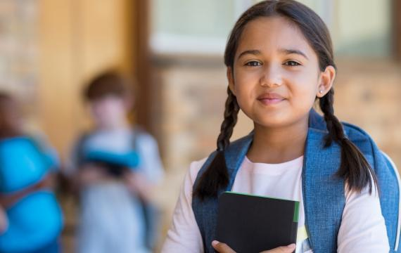 young girl at school holding a notebook