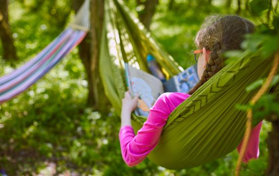 girl in hammock reading a book summer reading programs seattle-area libraries fun for kids and families