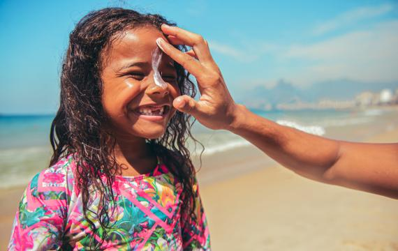 little smiling girl on the beach with her mom's hand swiping sunscreen down her nose