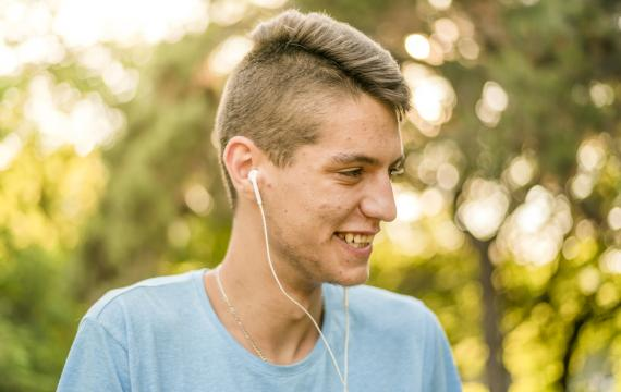 teen with acne scars smiling outdoors with headphones in his ears