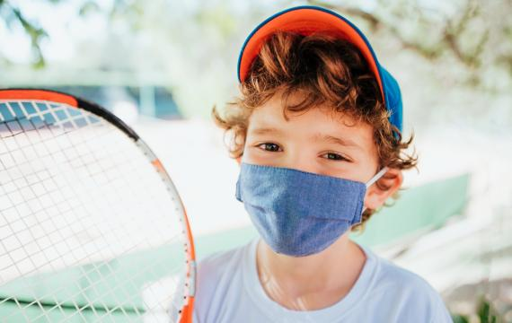 boy holding a tennis racket wearing a mask