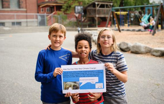 3 giddens students holding a climate change poster