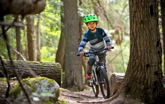 Boy in green helmet mountain biking in the woods best weekend events kids seattle, bellevue, tacoma
