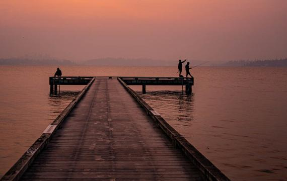 people fishing off a dock on Lake Washington during Seattle smoke haze from wildfires September 2020