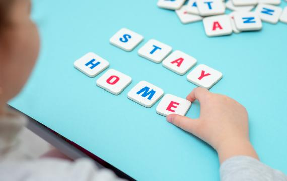 "Girl spells out the words ""Stay Home"" with tiles"