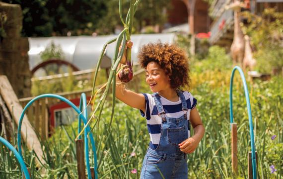 black girl standing in a garden holding an onion she just harvested