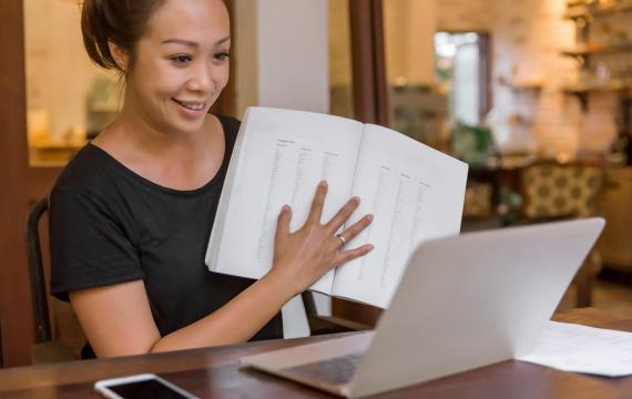 woman teaching in front of her laptop smiling