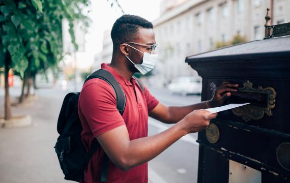 black teen wearing a mask putting his ballot in the mail