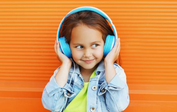 Smiling young girl listens to a podcast through headphones