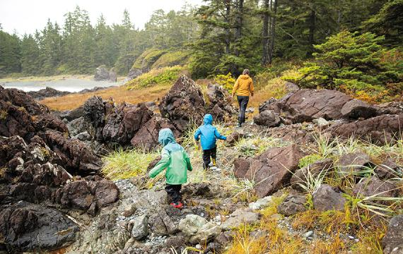family hiking over rocks with evergreen trees around