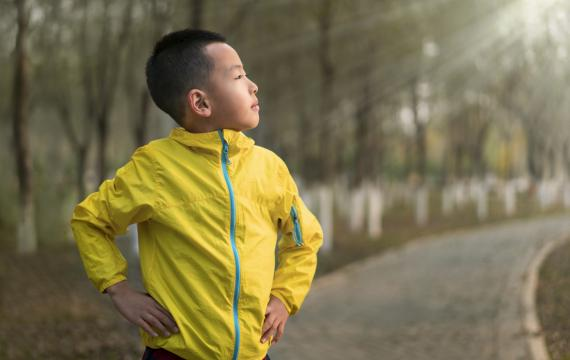 Contented-looking Asian boy about age 9 or 10 wearing a yellow rain jacket looking into the distance on a winter day best Seattle weekend events for families