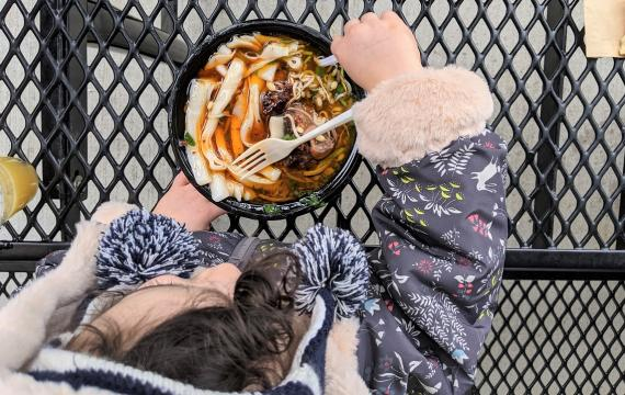 Young girl in flowered jacket eats ox tail noodle soup from Spice Bridge Food Hall in Tukwila Washington near Seattle