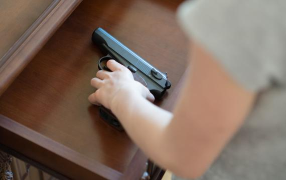 child's hand on a gun inside a drawer