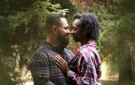 interracial couple with their noses together with pine trees in the background