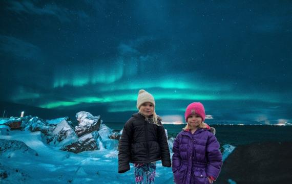 Two girls in winter coats and hats shown in front of a background of the Northern Lights seen in Iceland in this photoshopped virtual travel image