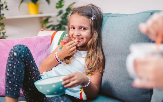 smiling girl sitting on the couch with a bowl of snack food
